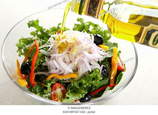 Oil being poured on bowl of vegetable salad