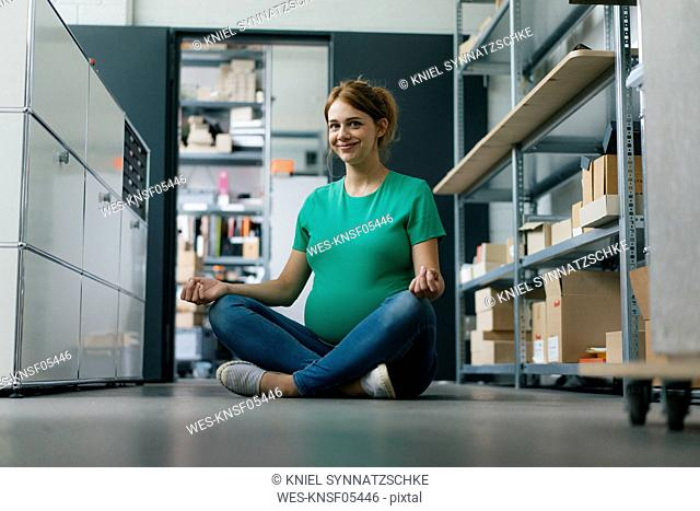 Smiling pregnant woman sitting on floor in office having a yoga break
