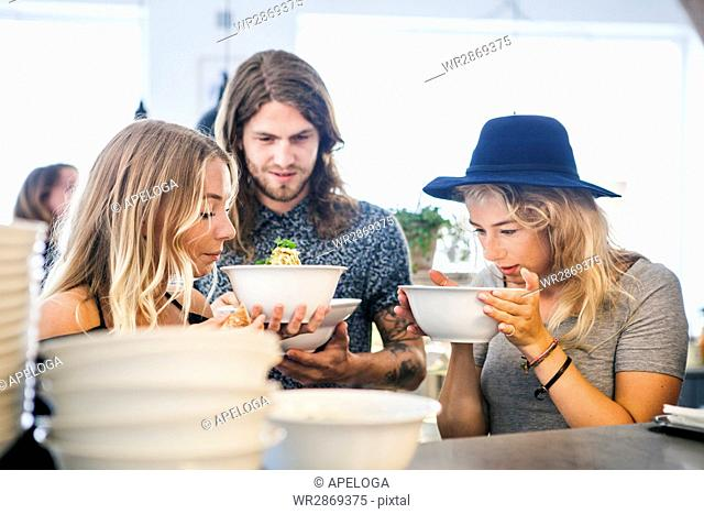Male and female friends smelling food in restaurant