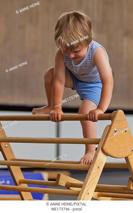 2 year old boy climbing a ladder in a gym. Germany