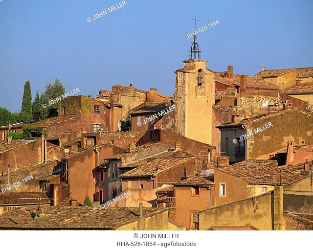 Church bell tower above the roofs of houses in the village of Roussillon in Provence, France, Europe