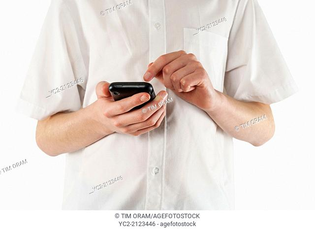 A teenage boy texting on a smartphone