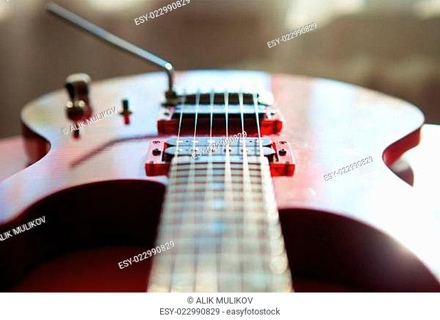Red electric guitar laying on a red velvet
