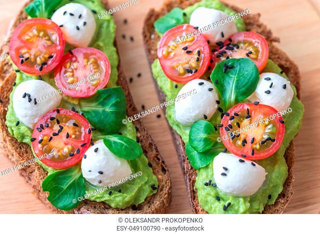 Sandwiches with avocado paste, cherry tomatoes and mozzarella