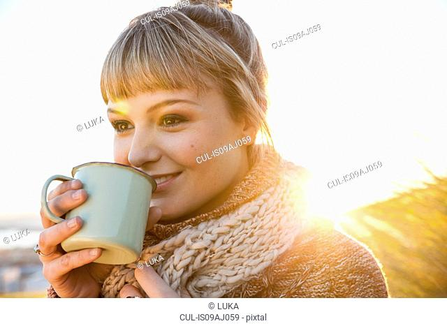 Portrait of young woman in sunlit marsh with drinks mug