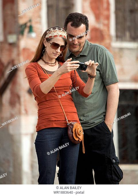 Italy, Venice, Couple viewing digital camera in city