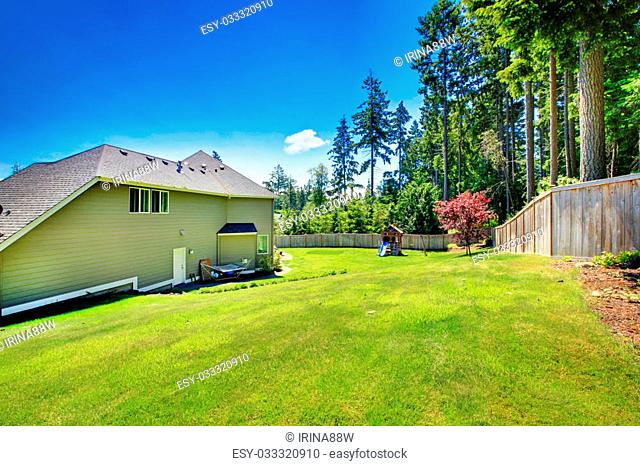 Spacious fenced backyard area with play set for kids on green lawn