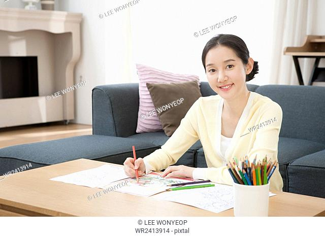 Portrait of young smiling woman drawing pictures staring at front
