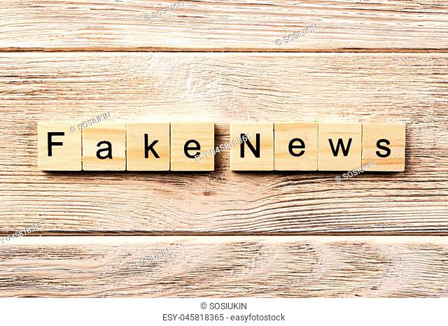 fake news word written on wood block. fake news text on table, concept
