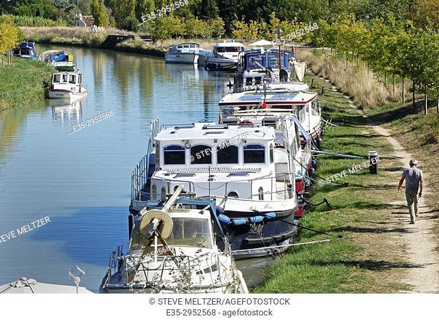 A man walks passed boats moored along the canal du Midi at Capestang, France