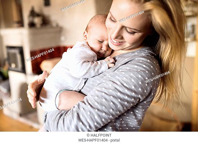 Happy mother holding baby at home