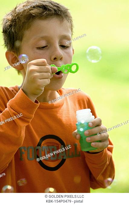 Boy blowing bubbles at a park