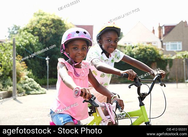 Portrait happy brother and sister riding bikes in sunny neighborhood