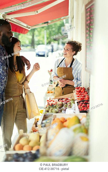 Female worker helping young couple shopping for fruit at market storefront