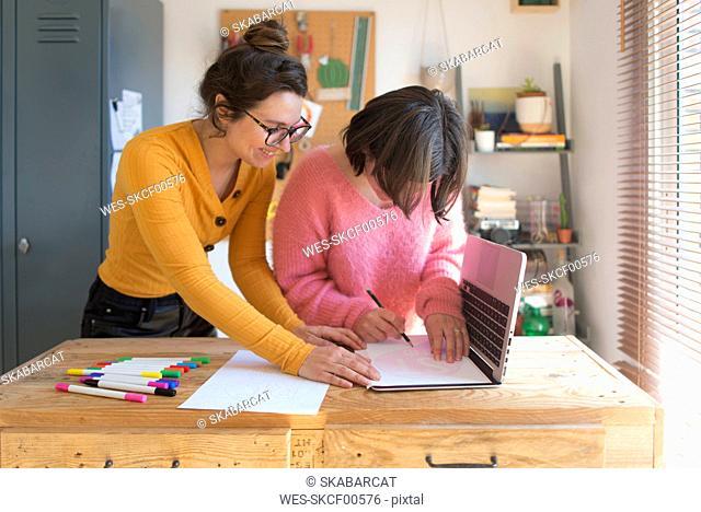 Two women drawing stencils for printing sweatshirts