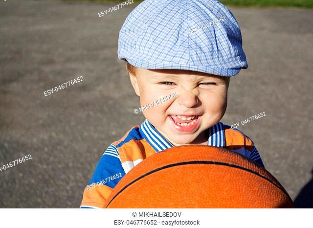 a little boy holds a basketball, a street basketball Playground
