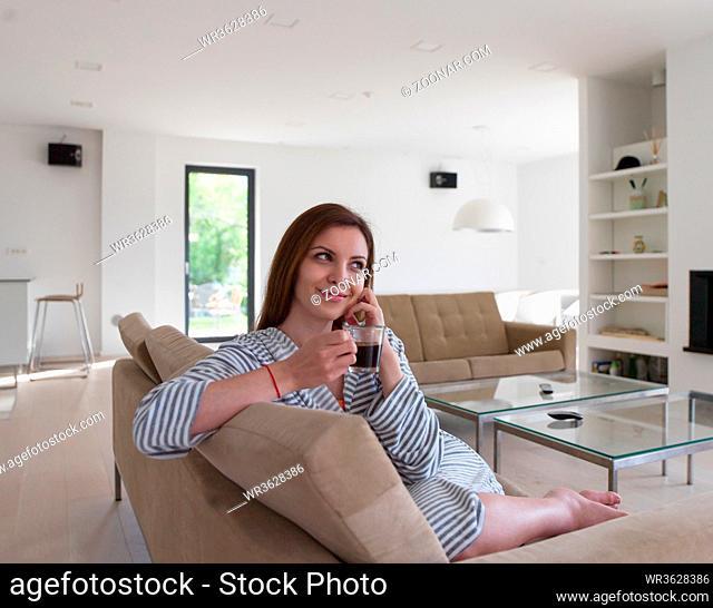 Beautifull young woman in a bathrobe enjoying morning coffee in her luxurious home villa