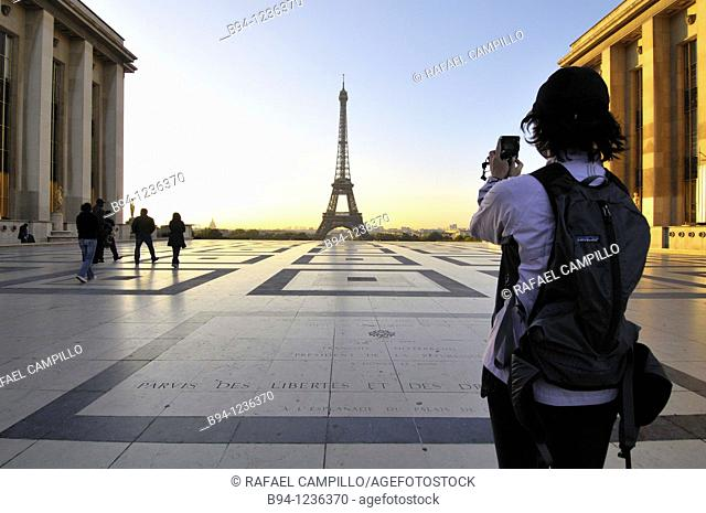 Girl taking a picture. Eiffel Tower from the Terrace the Rights of Man of Chaillot Palace. Paris, France