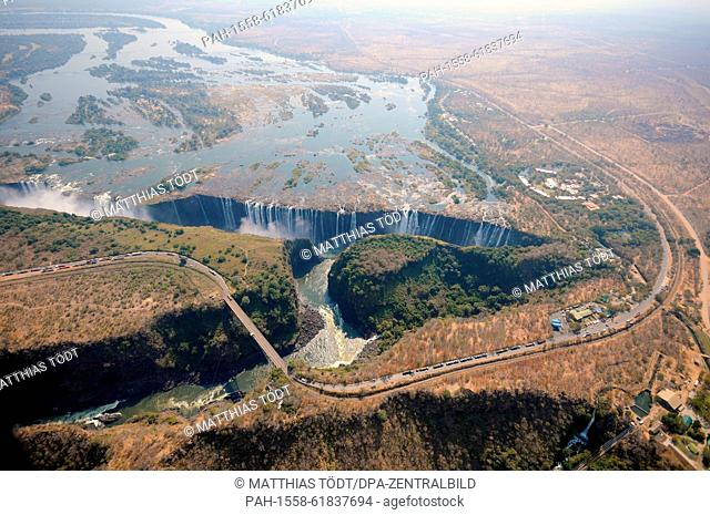 A view of the Victoria Falls and the broad course of the Zambezi River facing Zambia, with trucks on a road in the foreground waiting to enter Zambia
