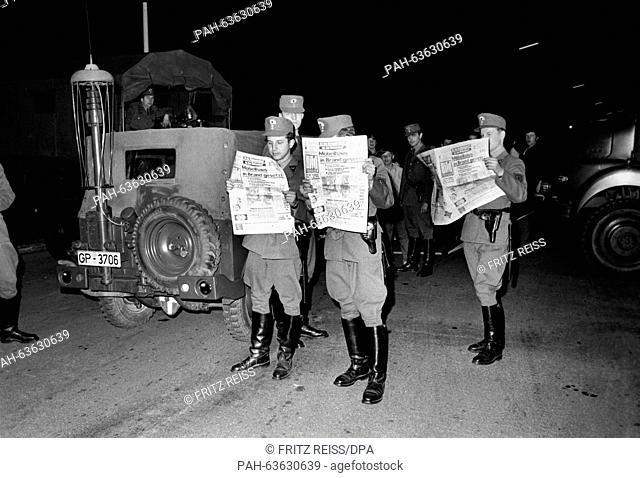 Policemen read the BILD newspaper in front of the Sprinter printing house. Participants of a demonstration on Easter Monday try to block the newspaper delivery...