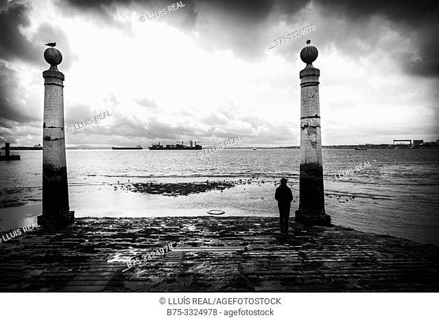 A man looking at the sea Cais das Colunas, Plaza del Comercio, Lisbon, Europe