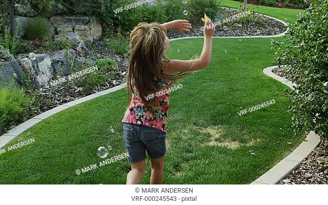 SLO MO WS Girl (6-7) playing with soap bubbles in garden / Cedar Hills, Utah, USA