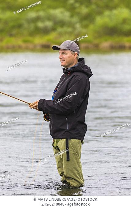 White man fishing, standing in the water, looking happy and smiling, Rautas river, Kiruna county, Swedish Lapland, Sweden