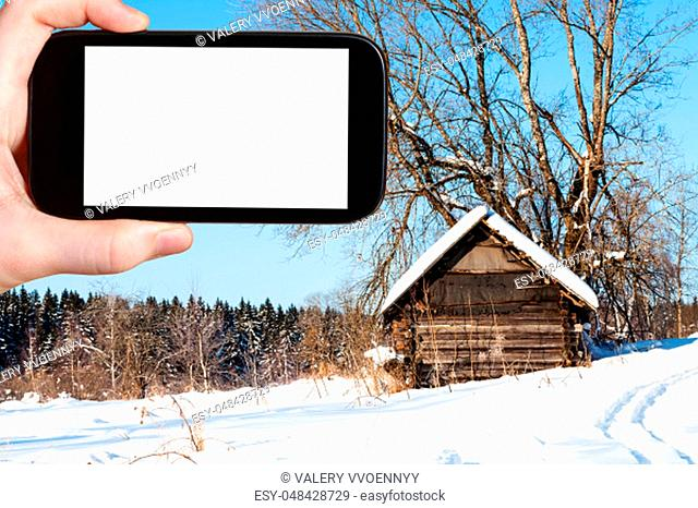 travel concept - tourist photographs of old abandoned wooden hut near forest in sunny winter day in little village in Russia on smartphone with cut out screen...