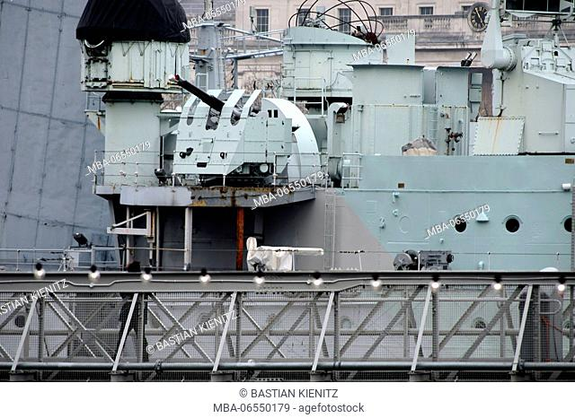 A woman entering the warship Belfast HMS on the shore of the Thames in London