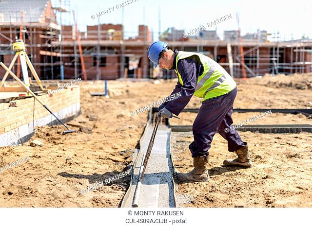 Apprentice builder laying concrete foundations on building site