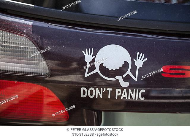 Funny graphic with 'Don't Panic' below it on the back of a car