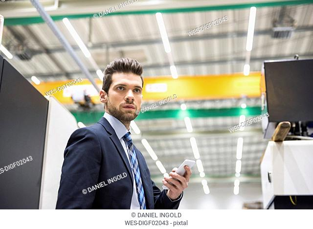 Businessman in factory shop floor holding cell phone