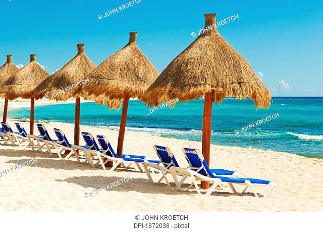akumal, mexico, lounge chairs and umbrellas on the beach facing the ocean
