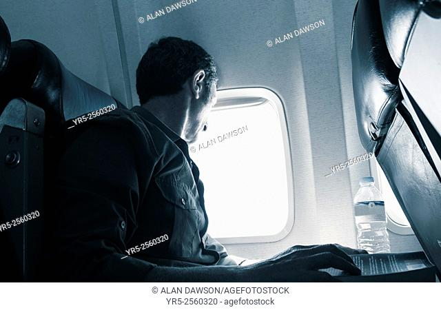 Mature man looking out of airplane window