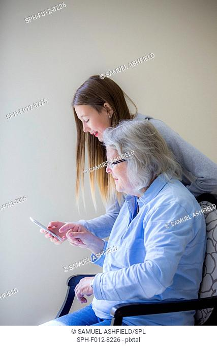 Teenage girl showing her grandmother how to use a smartphone
