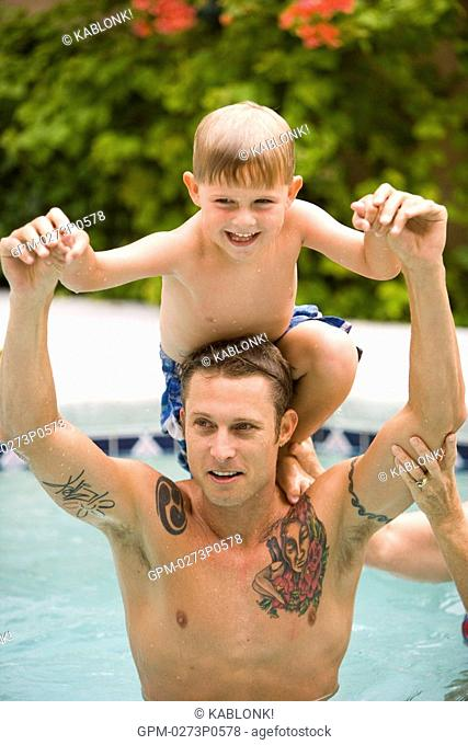Portrait of father and young son having fun together in swimming pool