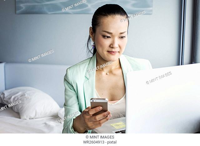 A business woman preparing for work, sitting on a bed using a laptop and holding her smart phone