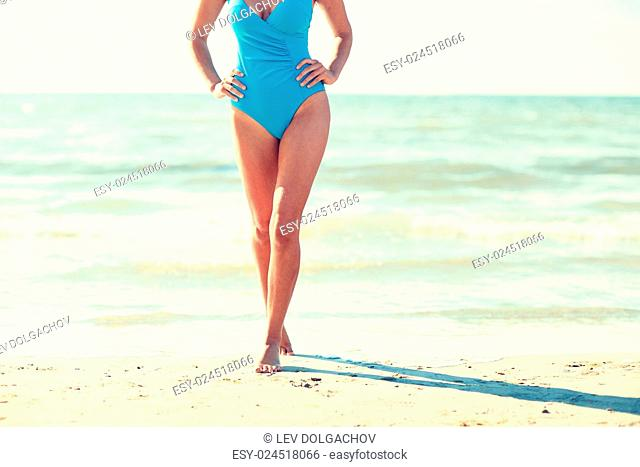 summer vacation, tourism, travel, holidays and people concept -close up of young woman in swimsuit walking on beach from back