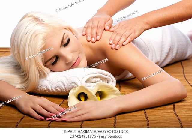 Beautiful young woman relaxing at spa getting therapeutic pampering shoulder massage