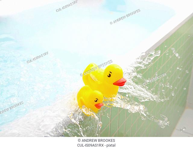 Rubber ducks falling out of bath overflowing with water