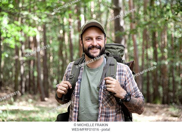 Portrait of smiling man with backpack on a hiking trip in forest