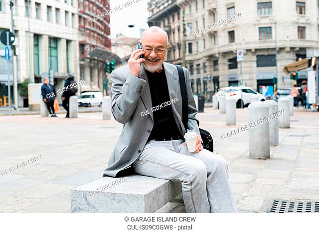 Businessman talking on smartphone in square, Milan, Lombardia, Italy