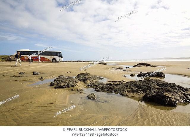 Aupori Peninsula Northland North Island New Zealand  Remote Ninety Mile Beach with rocks water pool wet sand tourists and parked coach at The Bluff on Tasman...