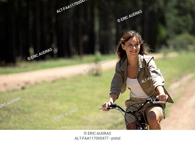 Young woman cycling in forest