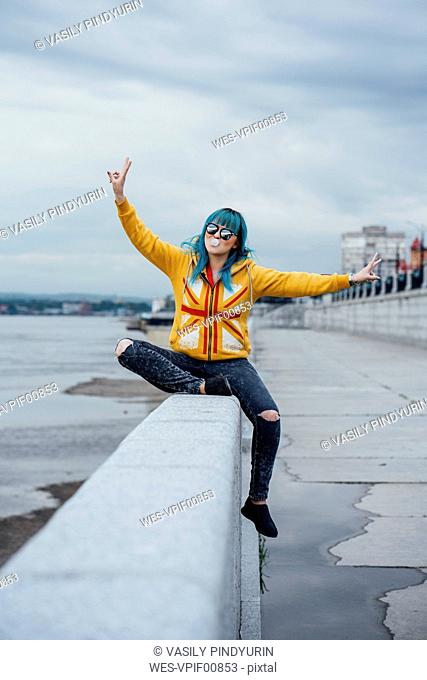 Portrait of young woman with dyed blue hair sitting on a wall showing victory signs