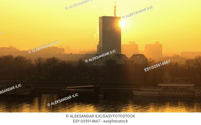 Sun going behind the building and view of the river Sava and urban scape of Belgrade city
