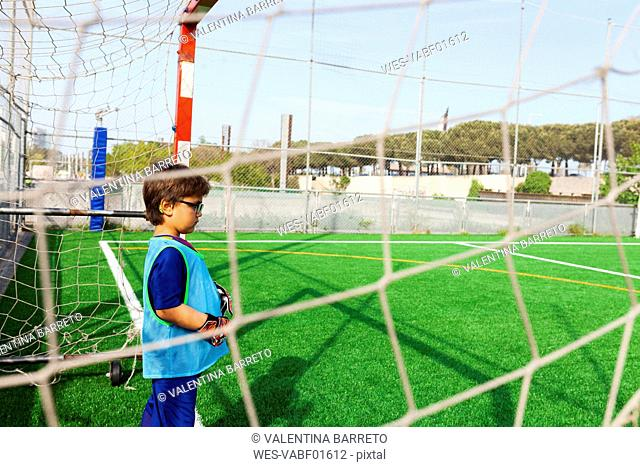 Little boy standing at goal on football ground