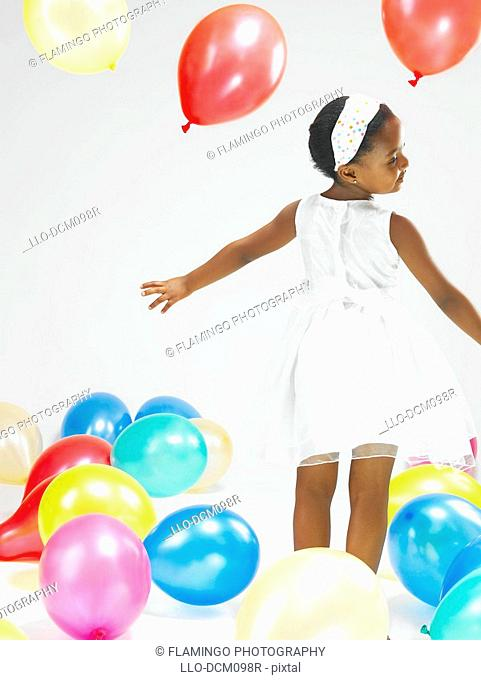Rear view of young girl standing with balloons