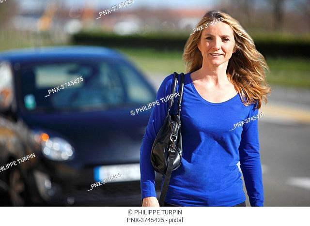 France, woman in front of her car