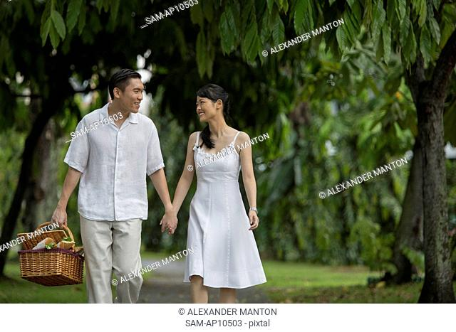 Singapore, Man wan woman with picnic basket walking through park